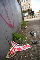 © Licensed to London News Pictures. 27/06/2019. London, UK. Police cordon tape lies on the ground near the Uxbridge Road in Shepherd's Bush where a teenager was fatally stabbed last night. Police were called at 9.20 PM on Wednesday, 26 June following reports of a stabbing. Officers found the male, believed to be aged 18 suffering from a stab injury but despite the efforts of paramedics the teenager died at the scene a short while later. Photo credit: Guilhem Baker/LNP