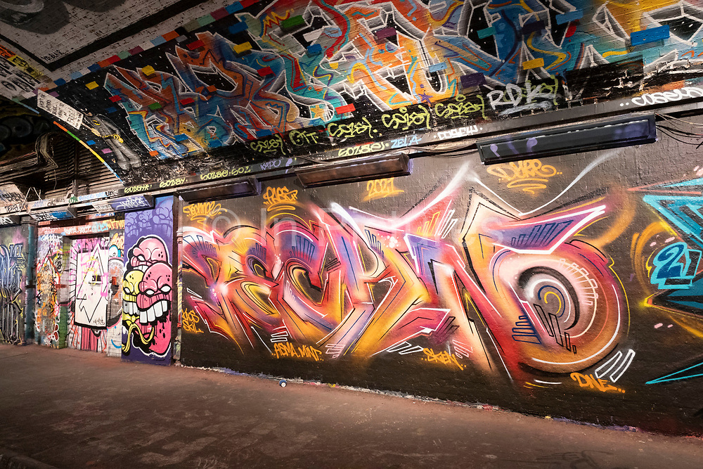 Spray painted street art and graffiti at the popular Leake Street Arches on 5th March 2021 in London, England, United Kingdom. Leake Street is a road tunnel in Lambeth, where graffiti is tolerated and encouraged regardless of the fact that it is against the law. The street is about 300 metres long, runs off York Road and under the platforms and tracks of Waterloo station.
