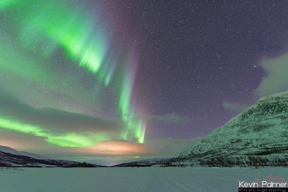 On this night I found myself in the Arctic wilderness of Abisko National Park in Swedish Lapland. After trekking for 9.5 miles I arrived in this stunning valley in the Scandinavian Mountains. The northern lights came out right away when night fell. But I had to wait for them to become more active and spread to the eastern sky over the 5,000' high peak named Kieron. That happened after 11:00, when bright auroral curtains shimmered across the sky, lighting up the snow and turning it green. The temperature hovered at -10°F and a stiff wind was blowing across the frozen Abiskojaure lake. But this captivating view was worth every step to get here and every moment of cold endured.