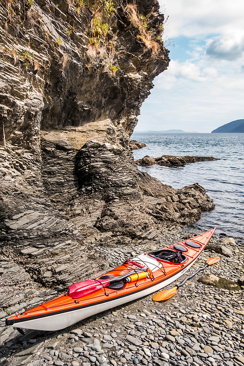 A sea kayak and paddles on a rocky beach, Orcas Island, Washington, USA. The Rosario Strait in the distance.
