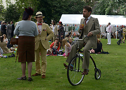 © Licensed to London News Pictures. 07/07/2012. London, UK  A man rides a penny farthing at 'The Chap's Olympiad' in central London on July 7th, 2012. 'The Chap' is a light-hearted magazine, aimed at revisiting the fashions and pastimes of the polite aspects of 1920's to 1950's England. The annual Olympiad event sees competitors take part in events such the 'Cucumber Sandwich Discus', 'The Umbrella Joust' and 'The Tug of Hair'e. Photo credit : Stephen Simpson/LNP