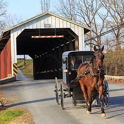 Paradise, PA, USA - December 6, 2015: An Amish buggy exits the Leaman's Place Covered Bridge which spans the Pequea Creek in Lancaster County, Pennsylvania.