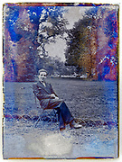 deteriorating glass plate of young adult man sitting in a public park France 1930s