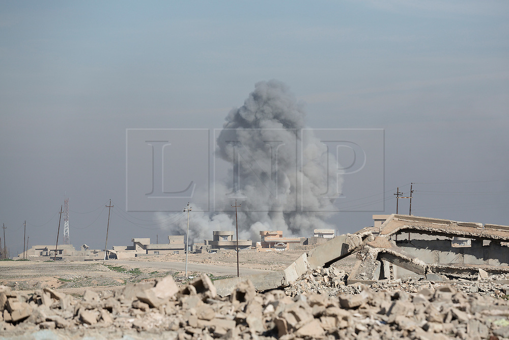 Licensed to London News Pictures. 20/02/2017. Albu Saif, Iraq. A large plume of dust marks the impact of a coalition forces air dropped bomb on the village of Albu Saif, Iraq. The bomb was dropped in support of Iraqi Security Forces who were assaulting the settlement as part of the offensive to retake western Mosul from the Islamic State.<br /> <br /> The settlement of Albu Saif is located on high ground overlooking Mosul Airport and as such is a strategic point that needs to be taken as part of the operation to retake the western side of Mosul. Photo credit: Matt Cetti-Roberts/LNP