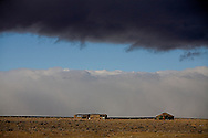 Traditional Hogan on the Navajo Reservation landscape with a winter storm passing through.