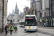 Passengers travel on a De Lijn electric tram on route 1 to Evergem on the Ghent tramway network in Ghent, Belgium.  The trams have been modernized to use less electricity and become more sustainable public transport. Some female pedestrians and cyclists past by the tram next the to old buildings.