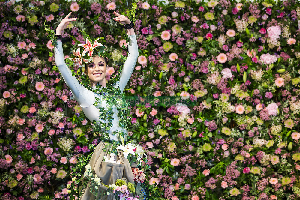 April 25, 2018 - Harrogate, Yorkshire, UK - Harrogate UK. Dancer Alison Parsons wears a flower dress in front of the flower wall in the Green House display at this years Harrogate Flower Show in which starts tomorrow. The GREENhouse has been designed to blur the lines between house and garden, creating a home infused with nature complete with living wallpaper,cascading flower shower, an aromatic bed of herbs and even a vege-table. (Credit Image: © Andrew Mccaren/London News Pictures via ZUMA Wire)