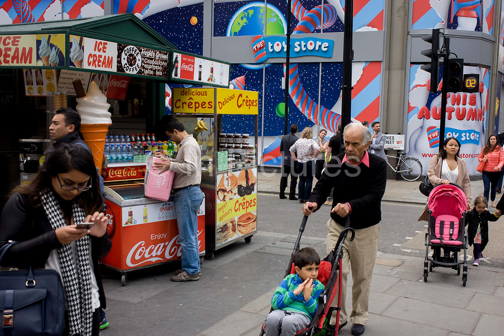 Incongruous urban landscape on central London's Oxford Street. Londoners and visitors to the capital fill the street, going about their business and walking past. A grandfather pushes a child's buggy, a woman checks her phone, a man fills a freezer with drinks at a regular kiosk selling ice cream cones and drinks and crepes. In the background are the bright colours of a construction hoarding for a new Toy Store on this busy street in Westminster, central London. There is a theme of striped poles and twisting design that helps lure the young and seduce their business when open soon.
