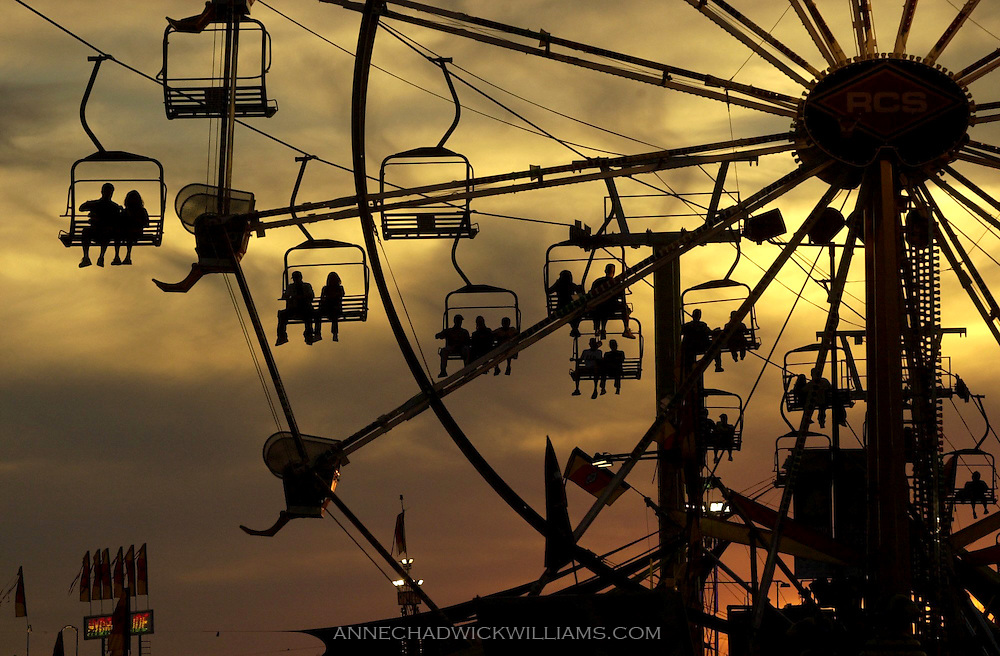 California State fair goers ride the sky ride from the midway across the fairgrounds as the sun sets. Anne Chadwick Williams / August 26, 2002.