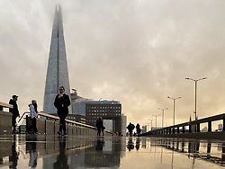 © Licensed to London News Pictures. 13/12/2020. London, UK. The tip of The Shard is covered with low clouds and reflection of people on a wet surface caused by rainfall in the capital. Photo credit: Dinendra Haria/LNP