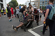 Two men playing on a pram falling over on Sunday 28th August 2016 at the 50th Notting Hill Carnival in West London. A celebration of West Indian / Caribbean culture and Europes largest street party, festival and parade. Revellers come in their hundreds of thousands to have fun, dance, drink and let go in the brilliant atmosphere. It is led by members of the West Indian / Caribbean community, particularly the Trinidadian and Tobagonian British population, many of whom have lived in the area since the 1950s. The carnival has attracted up to 2 million people in the past and centres around a parade of floats, dancers and sound systems.