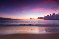 North Kaanapali Beach at sunset in late Spring at Maui, Hawaii as the waves roll on to the beach and the sky explodes with color.