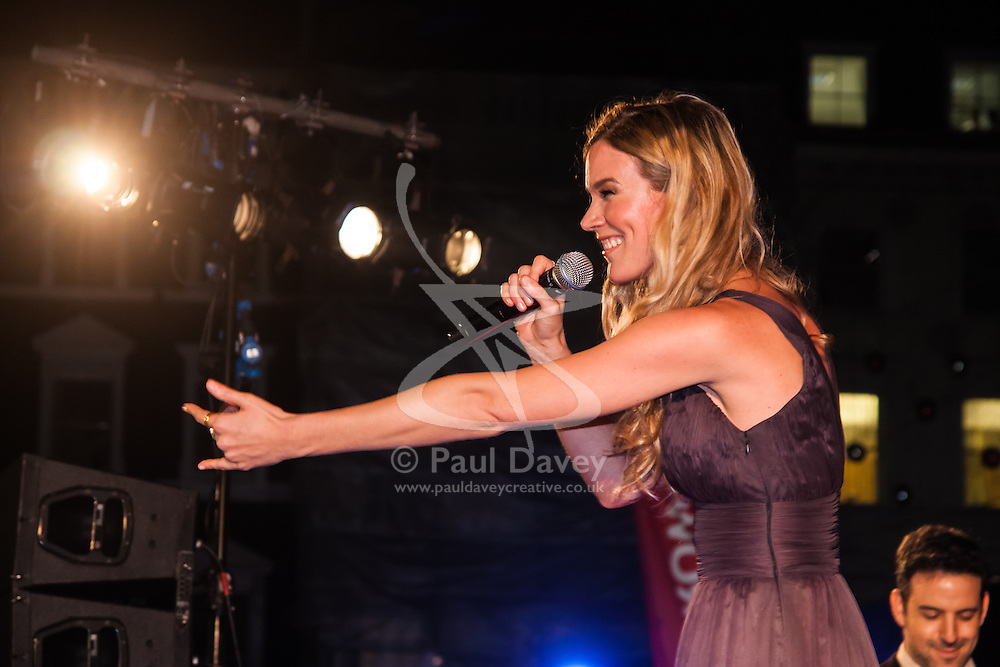 Covent Garden, London, October 30th 2014. Multi-platinum selling artist Joss Stone performs two numbers with legendary guitarist Jeff Beck as part of the events in Covent Garden where London Poppy Day events were held as the Royal British Legion raises funds, with over £1 million expected to be raised. PICTURED: Joss Stone beckons the crowd to come closer.