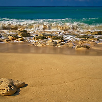 Breaking waves on Sandy Port Beach. Rocks and sand all on one beach