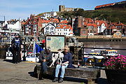Quayside at the harbour in Whitby, a seaside town, port in the county of North Yorkshire, originally the North Riding. Situated on the east coast at the mouth of the River Esk. Tourism started in Whitby during the Georgian period and developed. Its attraction as a tourist destination is enhanced by its proximity to the high ground of the North York Moors, its famous abbey, and by its association with the horror novel Dracula. Yorkshire, England, UK.