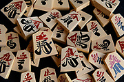 """A set of """"kaki-goma"""" (characters painted on with lacquer) shogi playing pieces. Nakajima Seikichi Shoten, Tendo, Yamagata Prefecture, Japan, February 19, 2018. The city of Tendo in Yamagata Prefecture is famous for its shogi (Japanese chess) playing pieces. Production started early in the 19th century and Tendo still produces over 95% of the Shogi pieces made in Japan."""