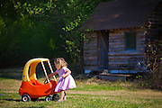 A young girl pulls a toy car across the grass on a farm in Chugiak, Alaska.