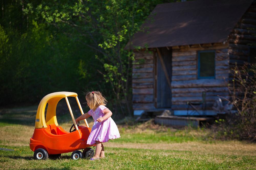 A young girl pulls a toy car across the grass on a farm in Chugiak, Alaska.