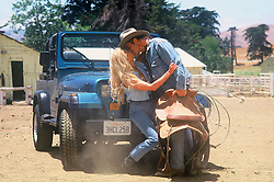 cowboy kissing a girl sitting on a jeep on a ranch