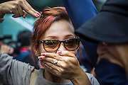 """01 JUNE 2014 - BANGKOK, THAILAND: Thais protest the loss of free speech by covering their mouths and putting their hands shaped as guns to their head during a protest against the coup in Bangkok. The Thai army seized power in a coup that unseated a democratically elected government on May 22. Since then there have been sporadic protests against the coup. The protests Sunday were the largest in several days and seemed to be spontaneous """"flash mobs"""" that appeared at shopping centers in Bangkok and then broke up when soldiers arrived. Protest against the coup is illegal and the junta has threatened to arrest anyone who protests the coup. There was a massive security operation in Bangkok Sunday that shut down several shopping areas to prevent the protests but protestors went to malls that had no military presence.    PHOTO BY JACK KURTZ"""