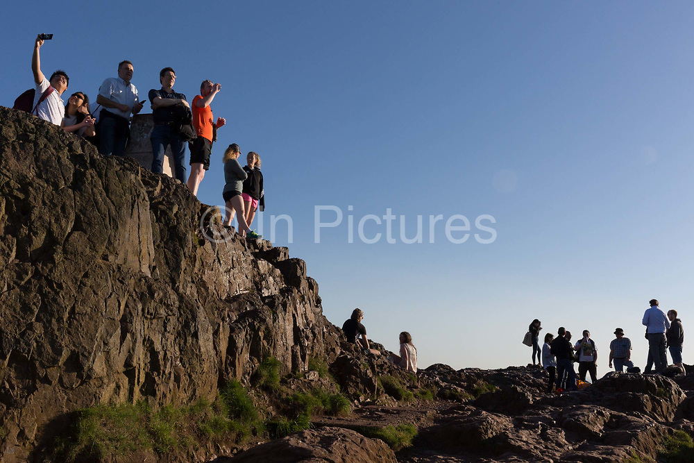 Walkers enjoy summer evening sunshine on the summit of Arthurs Seat in Holyrood Park, overlooking the city of Edinburgh, on 26th June 2019, in Edinburgh, Scotland. Arthurs Seat is an extinct volcano which is considered the main peak of the group of hills in Edinburgh, Scotland, which form most of Holyrood Park, described by Robert Louis Stevenson as a hill for magnitude, a mountain in virtue of its bold design. The hill rises above the city to a height of 250.5 m 822 ft, providing excellent panoramic views of the city and beyond.
