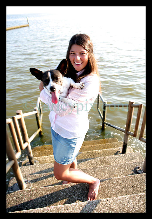 May 24th, 2006. Mandeville, Louisiana. 24 year old Gabrielle Garner with her parents dog Boudreaux. Gabrielle returned to rescue her dog from a local vet on Sept 1st, immediately after Hurricane Katrina struck the area.