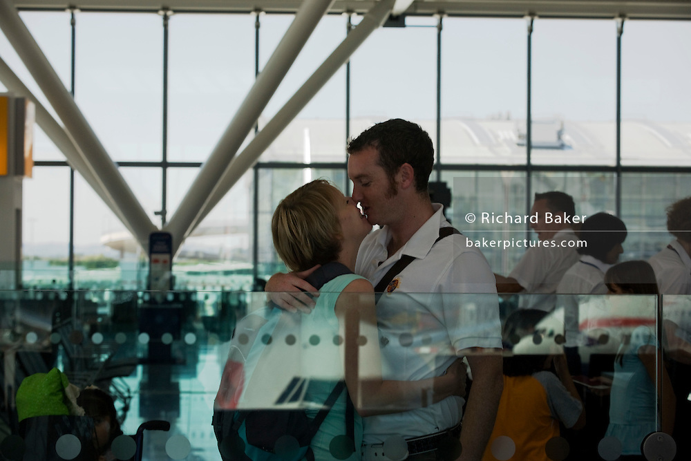 Honeymooners kiss before their round-the-world adventure departing from Heathrow Airport's Terminal 5B