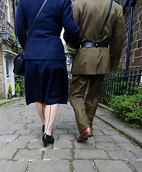 © Paul Thompson licensed to London News Pictures. 16/05/2015. Haworth, West Yorkshire, UK. back view of a man and woman, both in uniform during Haworth 1940s weekend, an annual event in which people dress in period costume and visit the village of Haworth to relive the 1940s. The woman has stockings with seams.  Photo credit : Paul Thompson/LNP