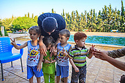 A member of the FSA teaches a group of children to salute with two fingers by the Swimming Pool of Marea on Wednesday, Jun 27, 2012. The two-fingered salute, or backwards victory or V-sign is the most frequent salute you see as a foreign photographer walking around the northern countryside of the Syrian Arab Republic, predominantly where the Free Syrian Army controls the territory. (Photo by Vudi Xhymshiti)
