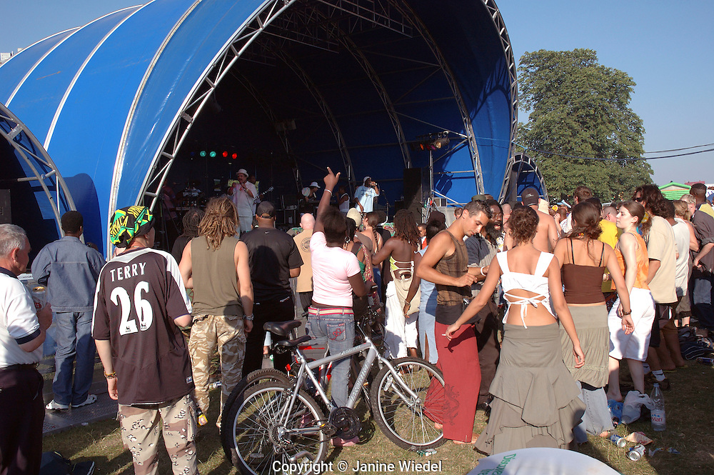 Young people dancing drinking and celebrating at festival in Brockwell Park South London.