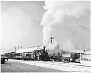 D&RGW K-28 with freight train in snow next to Durango freight house.  Several 1949-1950 automobiles parked nearby.<br /> D&RGW  Durango, CO  ca. 1950