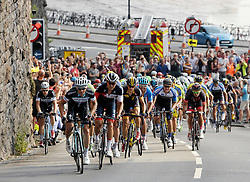 © Licensed to London News Pictures. 10/09/2014. Bristol, UK.  The Tour of Britain reaches Bristol.  Picture shows the peleton coming up the steep hill of Bridge Valley Road from the Avon Gorge with Brunel's Suspension Bridge towards the finish for the day. Photo credit : Simon Chapman/LNP