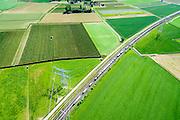 Nederland, Gelderland, Angeren, 09-06-2016; Boerenhoek, goederentrein verlaat tunnel onder Pannerdens kanaal van de Betuweroute. Pannerdensch kanaal (Neder-Rijn) aan de horizon.<br /> Tunnel Betuweroute, freight railway, Pannerdensch channel (Lower Rhine) on the horizon.<br /> <br /> luchtfoto (toeslag op standard tarieven);<br /> aerial photo (additional fee required);<br /> copyright foto/photo Siebe Swart