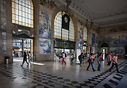 Beneath Azulejo tiles, travellers and commuters walk through the concourse of Sao Bento railway station, on 20th July, in Porto, Portugal. The name of the station derives from a Benedictine monastery built on this spot in the 16th century. The monastery fell victim of a fire in 1783, was later rebuilt, but was in a grave state of disrepair at the end of the 19th century. The most notable aspect of Sao Bento Station is the tile panels in the vestibule. There are some 20 thousand and date from 1905–1916, the work of Jorge Colaço, the most important azulejo painter of the time. The first tiles were put up on 13 August 1905.