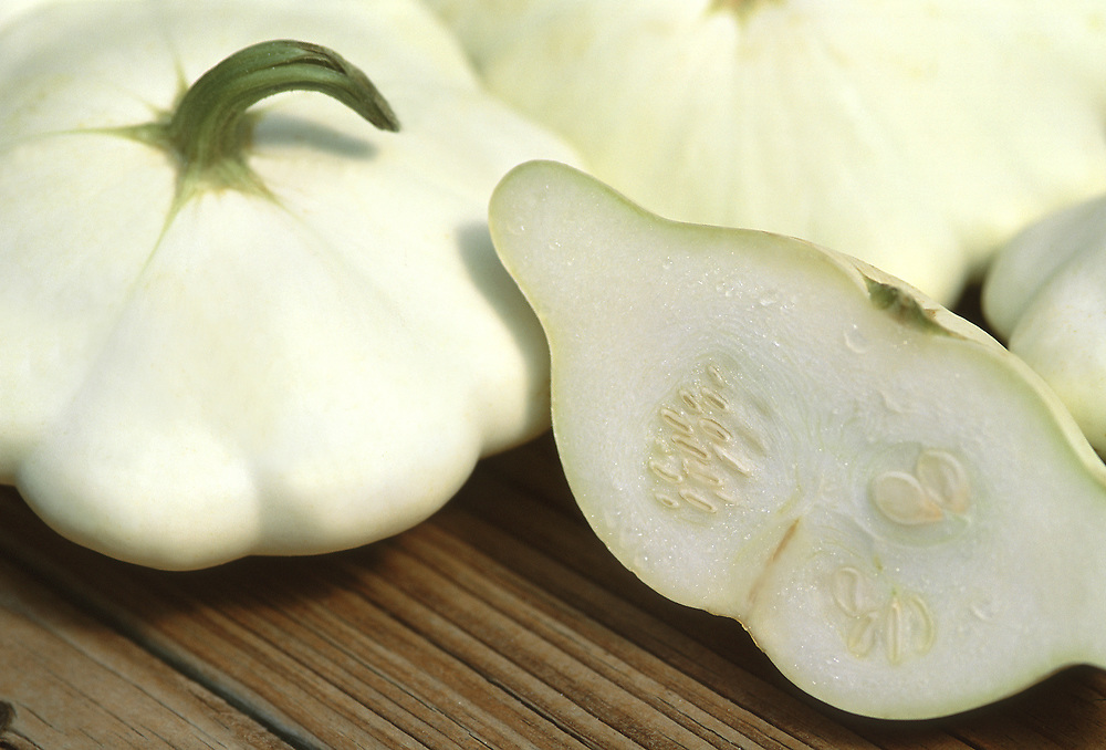 Close up selective focus photograph of a few Pattypan Squash on a table with one cut in half exposing the inside