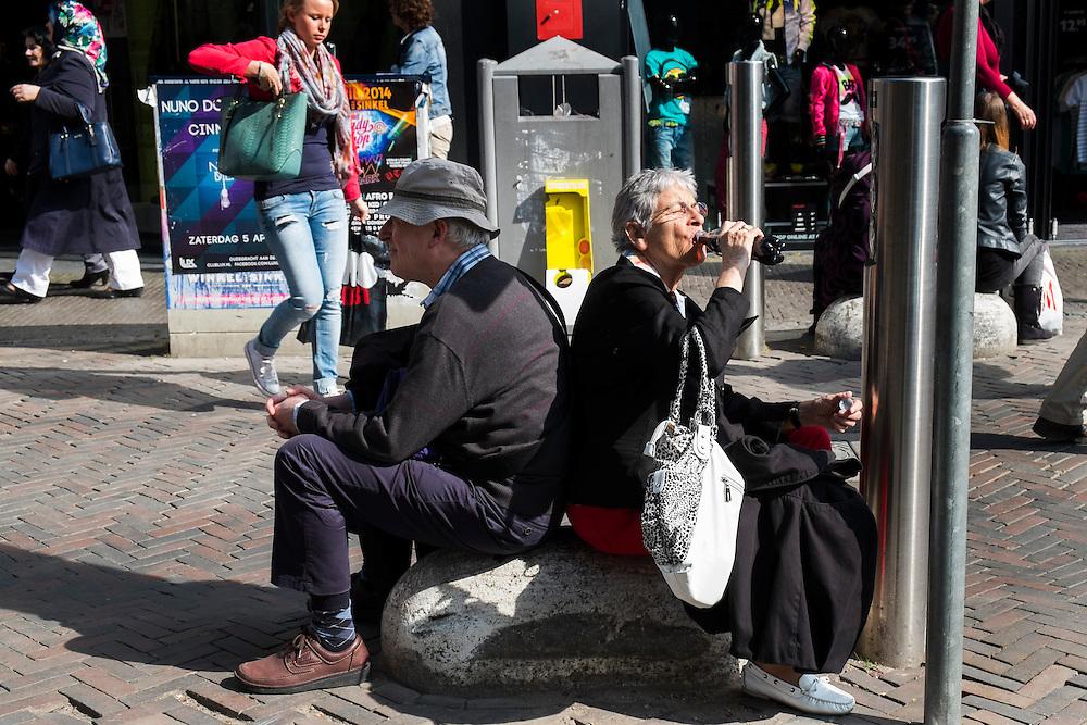 Nederland, Utrecht, 29 mrt 2014<br /> Ouder stel rust even uit op een betonblok op Vredenburg.<br /> Ze hebben 1 flesje cola en drinken daar om de beurt uit.<br /> Foto (c) Michiel Wijnbergh