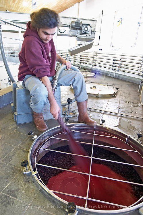 Pumping over, spraying the must on the skins and pips cap merlot chateau la dauphine fronsac bordeaux france