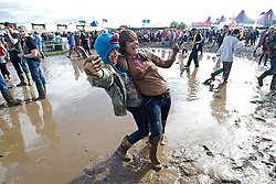 © Licensed to London News Pictures. 26/08/2011. Reading, UK. Rain soaked revellers battle through mud to enjoy day one of Reading Festival 2011 in Reading, Berkshire today (26/08/2011). Photo credit: Ben Cawthra/LNP