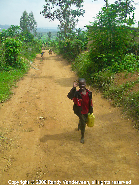 Kigali, Rwanda, A young Rwandan boy waves in greeting as he carries a container of water along one of the roads in an outlying area in Kigali, Rwanda.