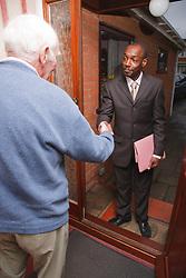 Older man welcoming visitor.