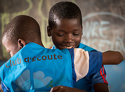 3 June 2019, Djohong, Cameroon: At the Ecole Publique de Borgop' (Public School of Borgop), children participate in 'the Listening Club', where today painter and consulting artist Dogari Samson leads a specific eight-day intervention to teach the children how to make drawings with images and messages of peace. Here, two boys share a congratulatory hug, as one of them has had his drawing selected as 'the best drawing of the day'. The Borgop refugee camp is located in the municipality of Djohong, in the Mbere subdivision of the Adamaoua regional state in Cameroon. Supported by the Lutheran World Federation since 2015, the camp currently holds 12,300 refugees from the Central African Republic.