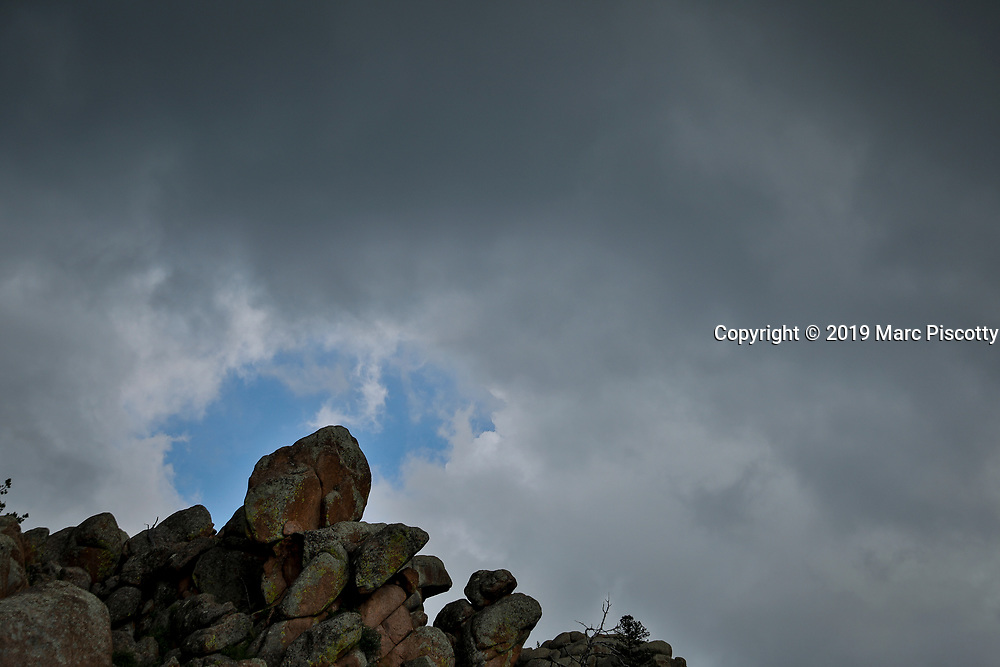 """SHOT 7/21/19 6:19:48 PM - A boulder is framed by a patch of blue sky along the Turtle Rock Trail at Vedauwoo Recreation Area. Vedauwoo is an area of rocky outcrops located in southeastern Wyoming, United States, north of Interstate 80, between Laramie and Cheyenne. Its name, according to some, is a romanized version of the Arapaho word """"bito'o'wu"""" meaning """"earth-born"""". (Photo by Marc Piscotty / © 2019)"""