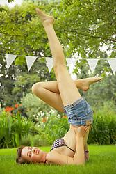 Teenage Girl Doing Shoulder Stand in Garden