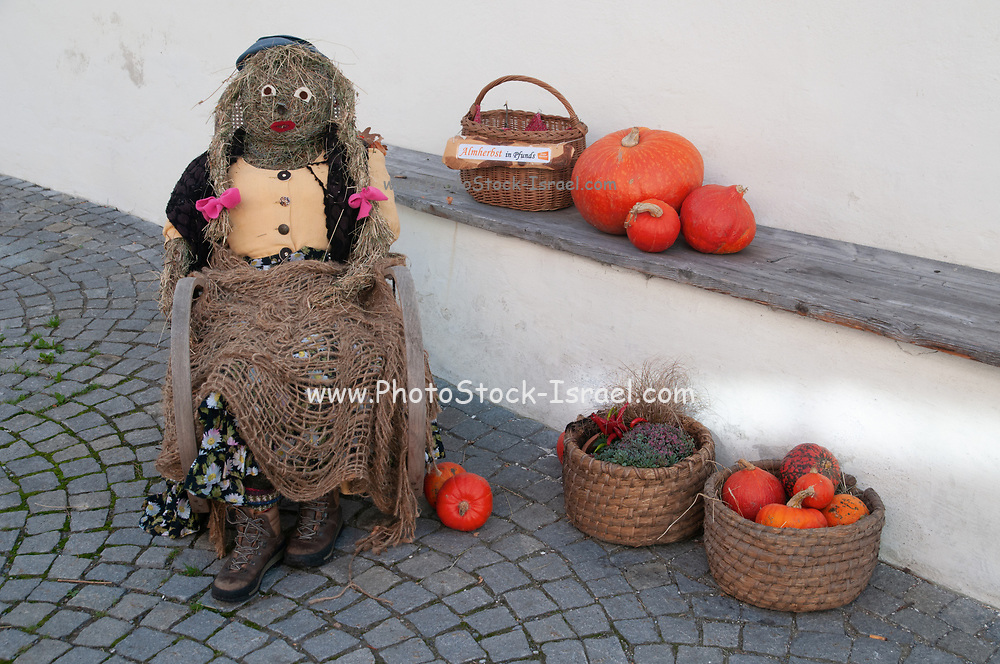 straw Halloween witch and pumpkins on display