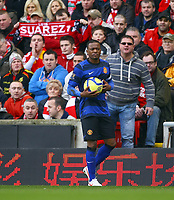 Football - FA Cup Fourth Round - Liverpool vs. Manchester United<br /> A Liverpool fan holds up a Luis Suarez scarf whilst another appears to hurl abuse at Patrice Evra of Manchester United at Anfield