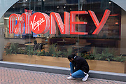 Man tying his show laces outside a Virgin Money store on 24th March 2021 in Birmingham, United Kingdom. Virgin Money is a financial services brand used by three independent brand-licensees worldwide.