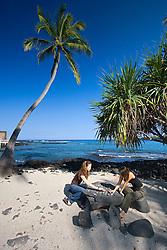 "Visitors playing Konane, an old Hawaiian ""checker"" game on stone table, Pu`uhonua o Honaunau or Place of Refuge National Historical Park, Honaunau, Big Island, Hawaii"