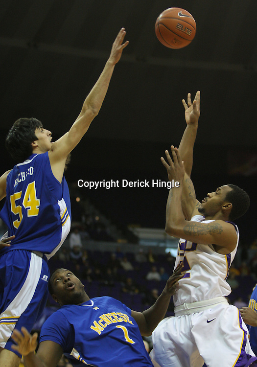 Jan 04, 2010; Baton Rouge, LA, USA; LSU Tigers guard Aaron Dotson (12) shoots over McNeese State Cowboys players Jeremie Mitchell (2) and Daniel Richard (54) during the first half at the Pete Maravich Assembly Center.  Mandatory Credit: Derick E. Hingle-US PRESSWIRE