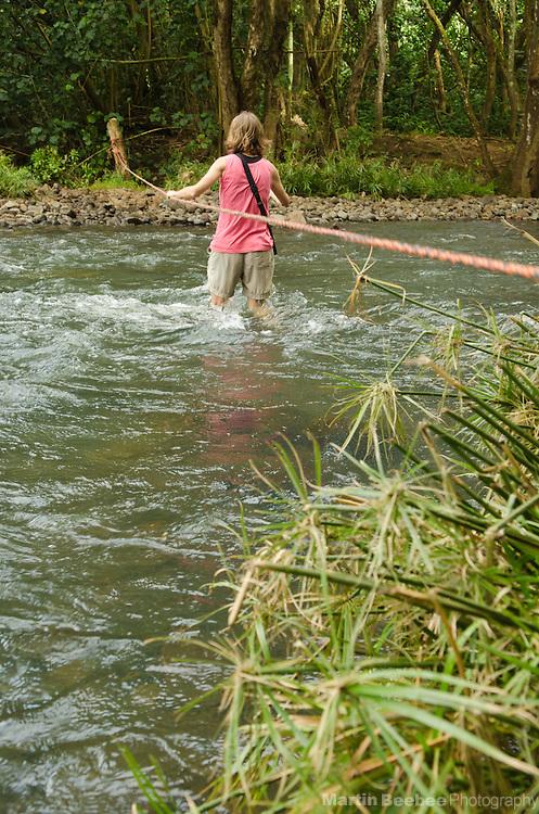 Woman crossing the Wailua River with a rope on her way to Secret Falls, Kauai, Hawaii