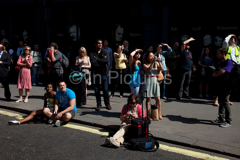Onlookers gather to watch the scene unfold. Fire in a large building which was under refurbishment at Aldwych, in central London. Seventy-five firefighters are tackling the blaze on top of the building in London's West End, at the junction of the Strand and Aldwych. The fire took hold around 11am this morning in a 10-storey building which is currently being converted to a 5-star hotel and 86 luxury flats. Transport for London has closed areas nearby and has put in place diversions.